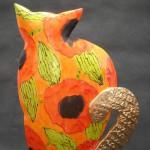 Siedzący kot (pomarańczowy w maki)